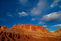 731350053 sunset light turns the sandstone formations of the waterpocket foldl red and gold in capitol reef national park in utah