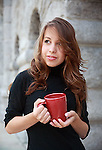 beautiful young woman with long brown hair holds a coffee cup outdoors in morning shade