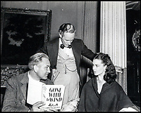 BNPS.co.uk (01202 558833)<br /> Pic:  Juliens/BNPS<br /> <br /> Director Victor Fleming holding the novel 'Gone With The Wind' while in discussion with Leslie Howard and Vivien Leigh.<br /> <br /> Amazing behind the scenes photos of the classic film Gone With The Wind have come to light 80 years later.<br /> <br /> The comprehensive archive of over 800 images includes candid snaps of the leads Clark Gable and Vivien Leigh unwinding between takes.<br /> <br /> One extraordinary photo shows the pair still in costume playing a board game, with another capturing the burning of Atlanta in the film.<br /> <br /> There is also a picture of the director Victor Fleming holding the novel 'Gone With The Wind' while in discussion with Leigh.