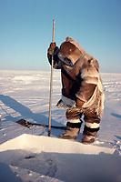 Kigutikaarjuk, an Inuit hunter, uses an ice chisel to make a hole in the ice for ice fishing Igloolik, Nunavut, Canada, Arctic