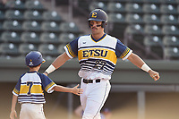 Right fielder Aaron Maher (27) of East Tennessee State is greeted by 10-year-old Gehrig Skole, son of head coach Tony Skole, after hitting a home run in a game against Samford at the Southern Conference Baseball Championship on Saturday, May 27, 2017, at Fluor Field at the West End in Greenville, South Carolina. ETSU won, 16-6. (Tom Priddy/Four Seam Images)