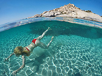 Υoung woman swims at the bottom of an exotic beach on half underwater view