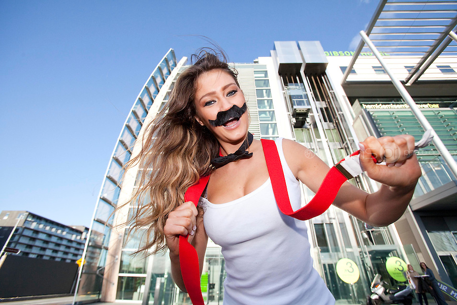 "NO REPRO FEE. 10/11/2011. Miss Universe Ireland Aoife Hannon is pictured at the Gibson Hotel Dublin in aid of Movember. The gibson hotel is rockin' a lot of Mo love this November all in aid of Movember, the phenomenal moustache growing global campaign to raise awareness and funds for men's health especially prostate cancer. Today, Thursday 10th November, ""Mo Bro' staff at the gibson hotel were joined by Miss Universe Ireland Aoife Hannon and Neil Rooney from Movember Ireland to show how the gibson hotel's Movember antics are ""growing"" along!One of Dublin's hippest venues, the gibson hotel right in the heart of our emerging music and cultural hub in the Docklands is proud to embrace Movember with gusto with 12 staff members signed up for the annual moustache growing challenge and the hotel will be donating €1 from every Bacardi Mojito and bottle of Corona sold during the month of November. They have also built a custom made ""Get your Mo On"" carnival board for anyone passing through the hotel to try on a mo , have their picture taken and make a donation to Movember. Picture James Horan/Collins"
