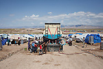 Syrian refugees collect water from a tanker inside the Domiz refugee camp in Iraqi-Kurdistan. The camp, run by the UNHCR and International Rescue Committee, is home to around 4,500 refugees who have fled from the ongoing Syrian civil war with up to 400 new inhabitants arriving every day.  Built on the site of a former Iraqi Army base that was bombed during the 2003 Coalition forces invasion of Iraq, the camp was cleared of cluster bombs and unexploded ordnance by the Mines Advisory Group (MAG), a demining NGO working in Iraqi-Kurdistan.