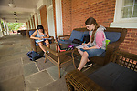 CIIS students Isabel Stafford, left, and Elli Grifferson take advantage of the Croft porch to study their Arabic as rain begins to fall.   Photo by Kevin Bain/Ole Miss Communications