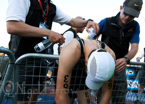 25 JUN 2011 - PONTEVEDRA, ESP - Officials pour water on the back and neck of Franz Loeschke (GER) at the finish of the Elite Men's European Triathlon Championships in Pontevedra, Spain in an attempt to help him cool down (PHOTO (C) NIGEL FARROW)