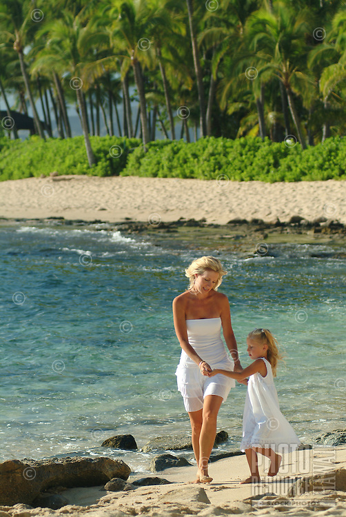 Mother and young daughter walking down beach togather while on vacation in Hawaii