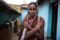 "Shombari Mahato, 36 years old, lives in Dhatkidih. In 2012, when she went to a local pond to wash herself, the other women in the village chased her away, asking her ""How many men have you eaten? Two or three?"". Few days before, she had been accused by a village widow of trying to kill her daughter. For security reasons, she accepted to be interviewed only far away from her house. The tattoo on her hand represents the symbol of the Adivasi tribe, it states that Adivasi will not take away anything from the earth when they die, except this tattoo, it is their only belonging."