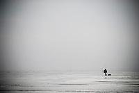 Lone Ice fisherman walking across a frozen Curonian Lagoon, Lithuania