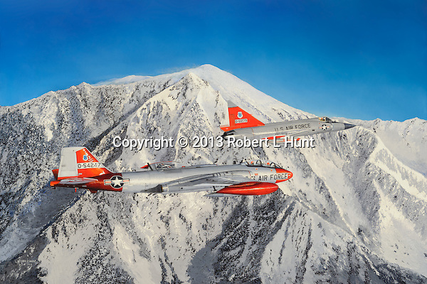 A B-57 bomber and F-102 fighter jet of the US Air Force flying above an Alaskan mountain range after completing a radar screen penetration training mission. The original 27x40 oil painting hangs in the aviation permanent collection in the Glenn L Martin Maryland Aviation Museum in Baltimore MD. <br /> <br /> Specifically: a U.S. Air Force Martin EB-57E Canberra of the 117th Defense System Evaluation Squadron, 190th Defense Systems Evaluation Group, Kansas Air National Guard, based at Forbes Air Force Base, Kansas escorts an Air Defense Command F-102.........<br /> <br /> Canvas reproductions are available; please call.