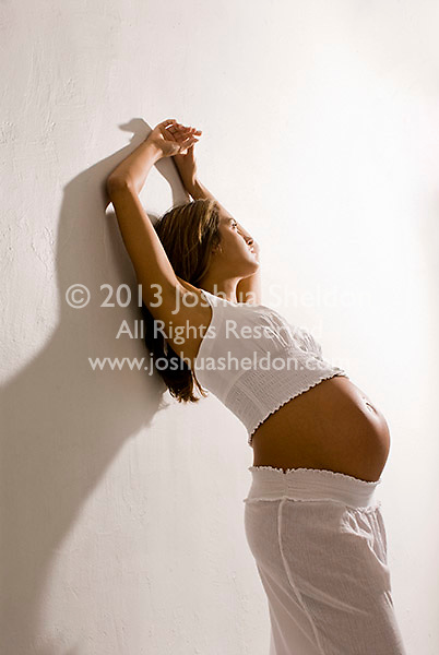 Portrait of young pregnant Hispanic woman, leaning her back against a white wall