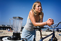 "Saturday, June 21 2009.  Pacific Beach, San Diego, CA, USA:  Anna Cummins of the environmental group Algalita Marine Research Foundation (AMRF) gets ready to make breakfast with her bicycle-powered blender on the beach in PB one day after completing a six-week journey from Vancouver to TJ with her husband Dr Marcus Eriksen, to raise awareness about marine debris.   The couple spoke at 40 different events along the way and presented 5 mayors with samples of the ""plastic soup"" that they collected form a remote part of the Pacific Ocean known as the North Pacific Gyre.  The confluence of currents in that area of the Pacific has created a high concentration of marine debris - particularly plastics - that is clogging the area, endangering marine life and entering our food chain."