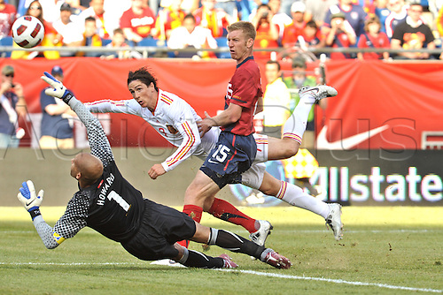 04.06.2011. Spain forward Fernando Torres (9) manages to get the shot off despite being bumped from behind by United States defender Tim Ream (15) and manages to get it past United States goalkeeper Tim Howard to score during the Spain game against the USA at Gillette Stadium in Foxborough, MA