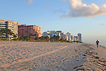 walker in Miami Beach at sunrise with hotels & condos in background