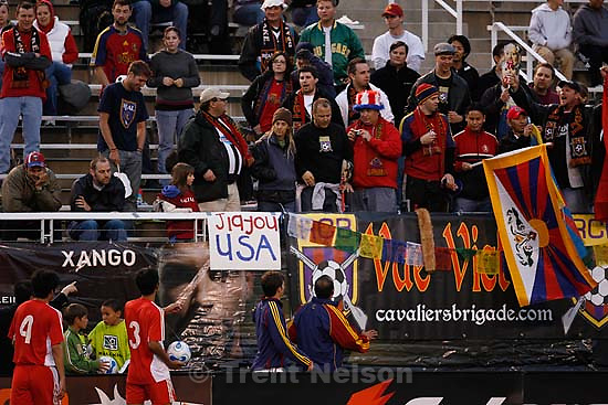 Salt Lake City - Real Salt Lake fans displaying Tibetan flags are confronted by Real employees during a stop in the second half of the game. Players on the Chinese team, including Li Tie (8, lower left) refused to resume play unless the flags were removed. Real Salt Lake vs. China (Chinese Men's National Team).