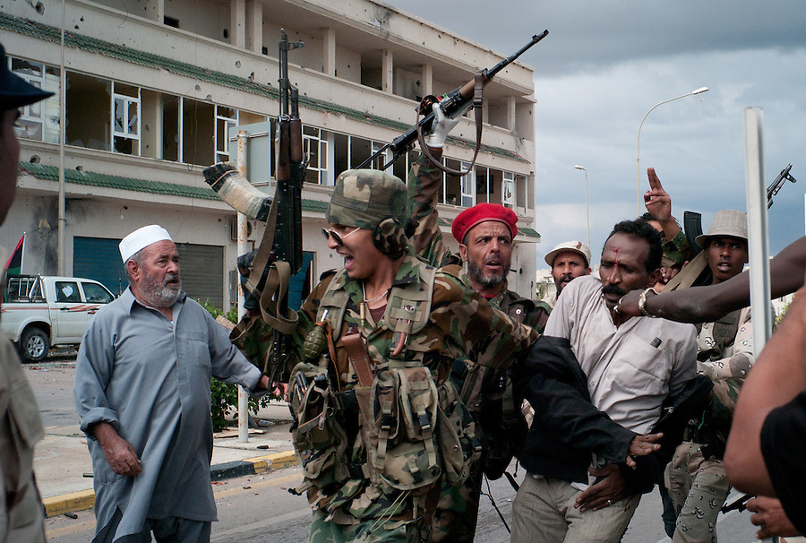 Anti-Gaddafi fighters with a suspected Gaddafi loyalist captured in Sirte, Libya.