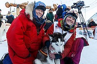 Lisbet Norris gives her lead dog Ruby a hug in the finish chute shorlty after finishing in 48th at Nome.  With her is her mother Kari Skogen who ran her first race 30 years ago. Saturday March 15 during the 2014 Iditarod Sled Dog Race.<br /> <br /> PHOTO (c) BY JEFF SCHULTZ/IditarodPhotos.com -- REPRODUCTION PROHIBITED WITHOUT PERMISSION