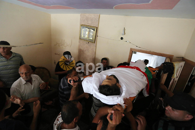 Palestinian mourners carry the body of Ahmed Qutoosh, 23, who died of his wounds endured during clashes with Israeli troops in a tent city protest where Palestinians demand the right to return to their homeland at the Israel-Gaza border, during his funeral in Nuseirat, in the central Gaza Strip, on May 25, 2018. Photo by Ashraf Amra
