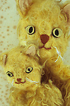 Heads and shoulders of homemade glove puppets of mother or father cat with kitten with matted golden fur and tatty whiskers