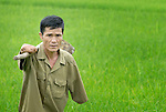 Nguyen Xuan Cuong, who lost his arms to a landmine during the U.S. war against Vietnam, walks through his rice field in Ha Trach, Vietnam.