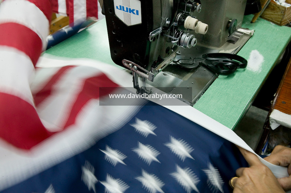 21 June 2005 - Oaks, PA - Idegonda Mauras (hidden) sows American flags together at the Annin & Co. flag manufacturing plant in Oaks, PA. Photo Credit: David Brabyn.