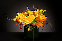 Elegant flower arrangement of yellow roses and orange lillies by floral artist Tomasi Boselawa