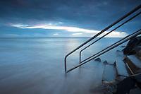 Waves washing over steps at Machans Beach, Cairns, Queensland, Australia