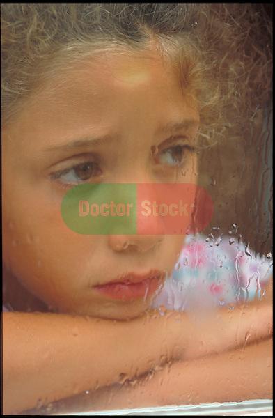 sad girl looking through rain covered window pane