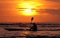 Man ocean kayaking enjoying the evening sunset