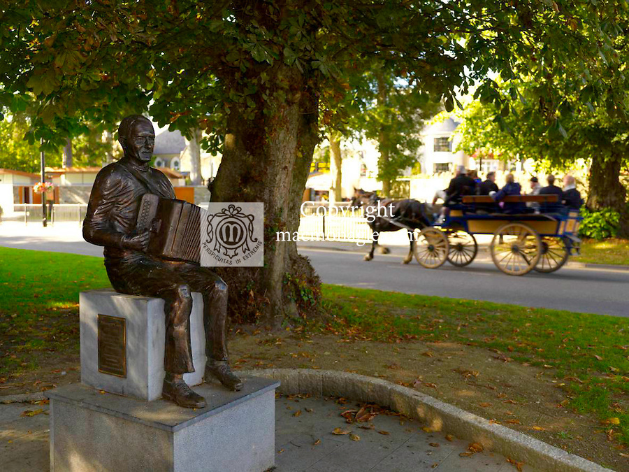 A jaunting car passes by the statue of Johnny O'Leary the famed Sliabh Luachra musician in Killarney  town centre this weekend ahead of the Tidy Town Awards..Picture by Don MacMonagle