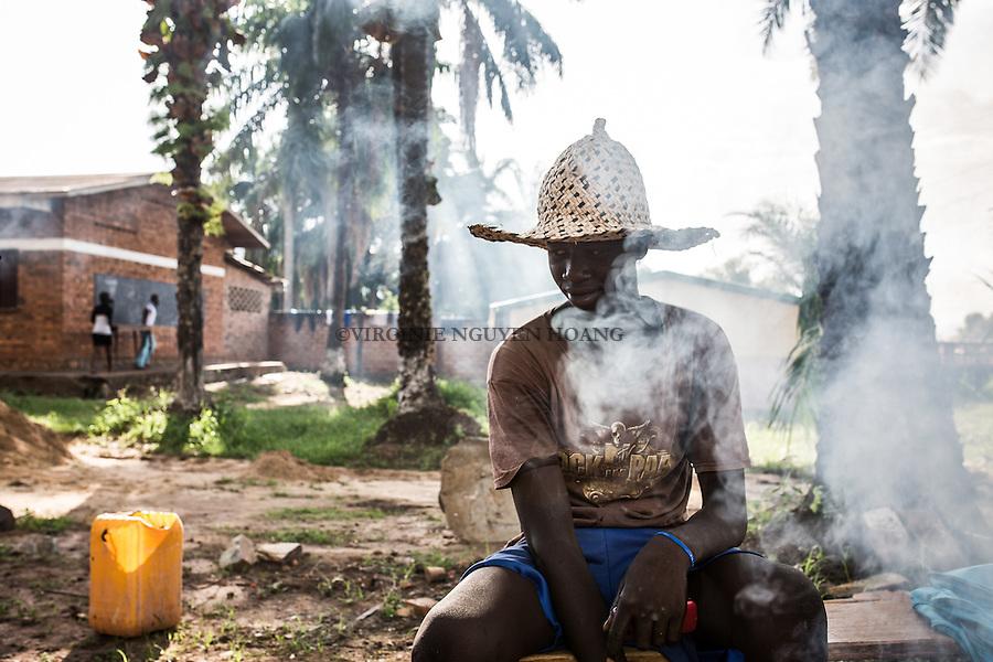 CAR, Bangui: A young man is cooking manioc for him and his friends that build red bricks. 20th April 2016<br /> RCA, Bangui : Un jeune homme cuit du manioc pour lui et ses amis qui construisent des briques rouges. 20 Avril 2016