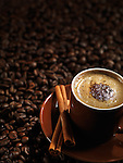 Cup of coffee latte with chocolate and cinnamon on coffe beans background