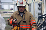 A fire chief with a radio on a fire scene