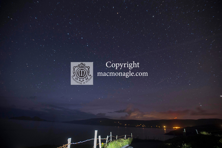 A stars filled night sky over St. Finan's Bay & The Glen in South Kerry near midnight during the annual perseid shower of shooting stars. One of the shooting stars can be seen as a white trace across the lower sky. The star cluster known as 'The Plough' can be seen centre left and the North Star is towards the top centre. This area of South Kerry is known as an International Dark Sky Reserve. The perseid shower happens when dust particles from the comet 'Swift-Tuttle' and happens every year around this time. The fence in the foreground is illuminated by a cars led parking lights while the red lights on the mountain are phone masts.<br /> Photo Don MacMonagle