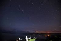 13-8-2017: A stars filled night sky over St. Finan's Bay &amp; The Glen in South Kerry near midnight during the annual perseid shower of shooting stars. One of the shooting stars can be seen as a white trace across the lower sky. The star cluster known as 'The Plough' can be seen centre left and the North Star is towards the top centre. This area of South Kerry is known as an International Dark Sky Reserve. The perseid shower happens when dust particles from the comet 'Swift-Tuttle' and happens every year around this time. The fence in the foreground is illuminated by a cars led parking lights while the red lights on the mountain are phone masts.<br /> Photo Don MacMonagle