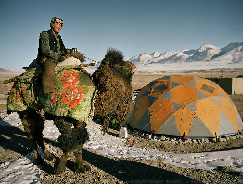 In the settlement of Qyzyl Qorum, Abdul Rashid' Khan (leader of the Kyrgyz) camp, Roshan (son of the Khan) passes on a camel the tent of US anthropologist Ted Callahan. .Winter expedition through the Wakhan Corridor and into the Afghan Pamir mountains, to document the life of the Afghan Kyrgyz tribe. January/February 2008. Afghanistan