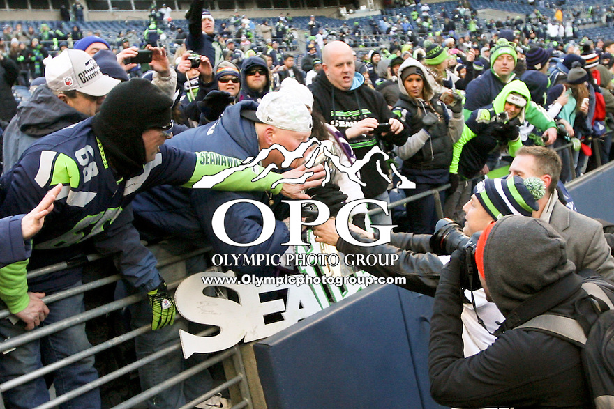 2014-02-05:  Seattle Seahawks Heath Farrell lets fans get an up close view of the Super Bowl Trophy. Seattle Seahawks players and 12th man fans celebrated bringing the Lombardi trophy home to Seattle during the Super Bowl Parade at Century Link Field in Seattle, WA.