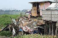 A boy looks out onto a destroyed home in one of the slum communities in central Jakarta. It was destroyed during the January floods which displaced approximately 20,000 people and caused the death of over 40 people. The slum communities are at great risk as many of them are found lining the city's waterways making them extreemly vulnerable to flooding.