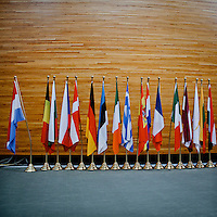 Country flags of member nations stand by the entrance to the main session hall at the European Parliament.