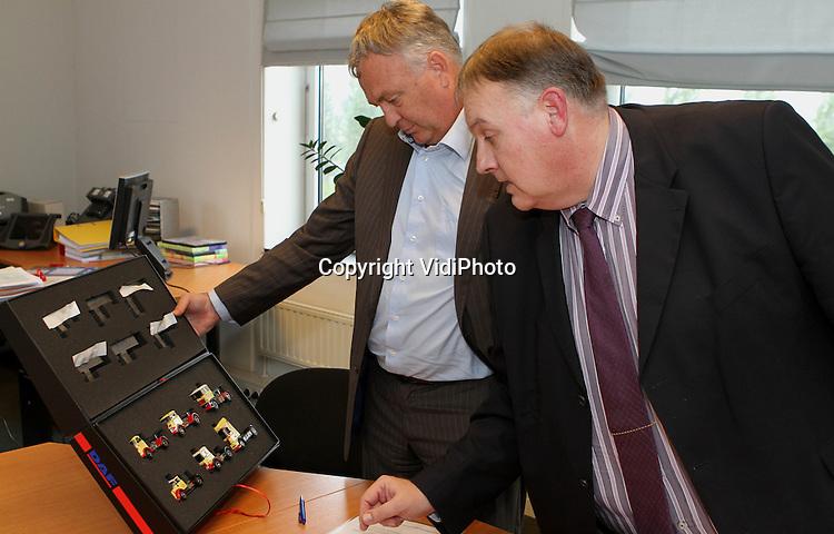 Foto: VidiPhoto..EDE - De directeuren van Brezan Automaterialen, Peter-Jan Stormmesand (l) en het Barneveldse transportbedrijf Van Reenen, Aart Hooijer, ondertekenen een contract voor samenwerking.
