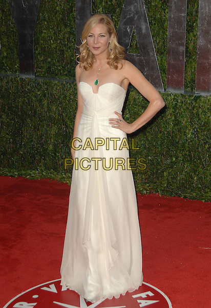 JENNIFER WESTFELDT .Attending The 2010 Vanity Fair Oscar Party held at The Sunset Tower Hotel in West Hollywood, California, USA, .March 7th, 2010                                                                                        .VF post arrivals oscars full length strapless off white cream dress hand on hip long maxi green stone necklace .CAP/RKE/DVS.©DVS/RockinExposures/Capital Pictures