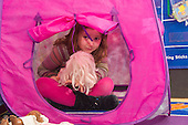 MR / Schenectady, NY. Zoller Elementary School (urban public school). Kindergarten inclusion classroom. Student (girl, 5) holding doll peeks out of play tent at free playtime. MR: Cas12. ID: AM-gKw. © Ellen B. Senisi.
