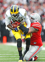 Ohio State Buckeyes defensive tackle Michael Bennett (63) takes down Michigan Wolverines quarterback Devin Gardner (98) in second quarter action at Ohio Stadium on November 29, 2014. (Chris Russell/Dispatch Photo)