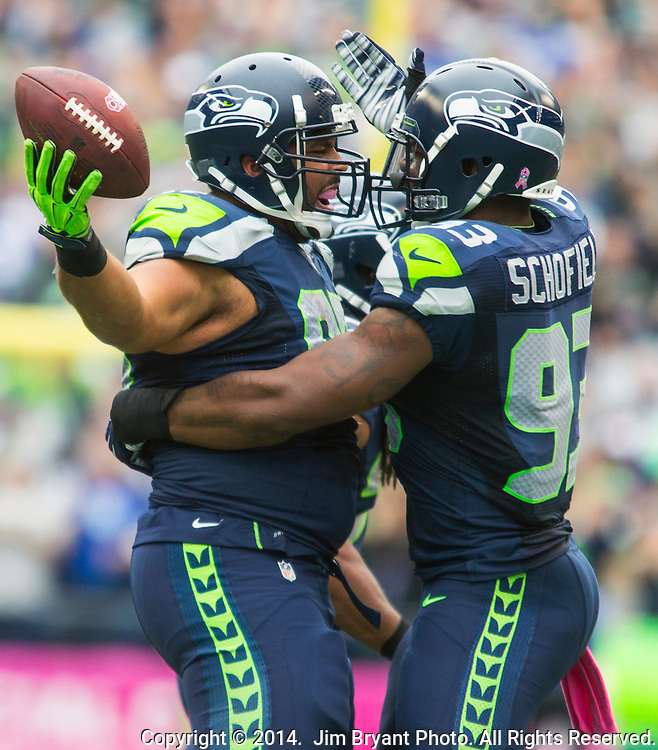 Seattle Seahawks  defensive tackle Jordan Hill (97) holds a Dallas Cowboys fumble as he celebrates with defensive end O'Brien Schofield (93)  at CenturyLink Field in Seattle, Washington on October 12, 2014. The Cowboys beat the Seahawks 30-23 .  ©2014. Jim Bryant Photo. All rights Reserved.