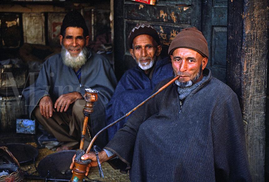 MUSLIM KASHMIRI MEN smoke a HUKKAH (hookah) in front of a small STORE - KASHMIR, INDIA.