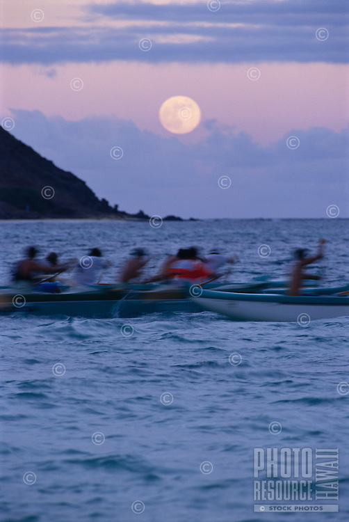 Hawaiian outrigger canoes in the ocean adjacent to Lanikai Beach, Oahu, Hawaii with the full moon rising behind.