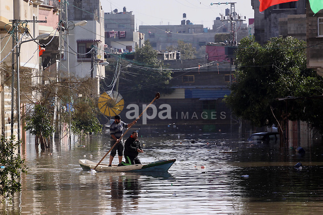 Palestinian rescue workers help residents move on a boat in Gaza City, Dec. 21, 2013. Rescue workers evacuated thousands of Gaza Strip residents from homes flooded by heavy rain, using fishing boats and heavy construction equipment to pluck some of those trapped from upper floors. Photo by Mohammed Asad