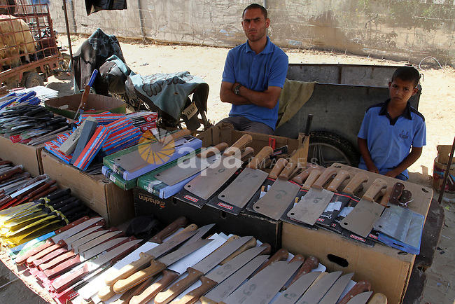 A Palestinian vendor displays knives  at a market, ahead of the Eid al-Adha festival, in Rafah in the southern gaza strip September 10, 2016. The knives use to slaughter cattle and sheep for the Muslim holiday of Eid al-Adha or the Feast of Sacrifice, which marks the end of the annual pilgrimage. Photo by Abed Rahim Khatib