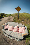 Sofa and chairs with four pink pillows abandoned along the roadway, road narrows sign near Ione, Calif.