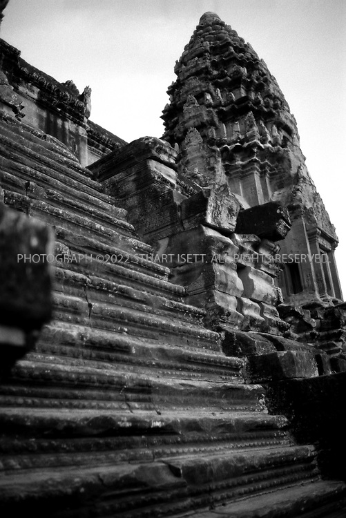 """4/20/2003--Angkor Wat Temples, Siem Reap, Cambodia..Angkor Wat on the upper level. Angkor Wat is located about six kilometers (four miles) north of Siem Reap, south of Angkor Thom. ..Angkor Wat was built in the first half of the 12th century (113-5BC). Estimated construction time of the temple is 30 years by King Suryavarman II, dedicated to Vishnu (Hindu), replica of Angkor Thom style of art...BACKGROUND .Angkor Wat, the largest monument of the Angkor group and the best preserved, is an architectural masterpiece. Its perfection in composition, balance, proportions, relief's and sculpture make it one of the finest monuments in the world. ..Wat is the Thai name for temple (the French spelling is """"vat """"), which was probably added to """"Angkor """"when it became a Theravada Buddhist monument, most likely in the sixteenth century (for the etymology of the name 'Angkor' see page 17) After 1432 when the capital moved to Phnom Penh, Angkor Wat was cared for by Buddhist monks. ..It is generally accepted that Angkor Wat was a funerary temple for King Suryavarman II and oriented to the west to conform to the symbolism between the setting sun and death. The bas-reliefs, designed for viewing from left to right in the order of Hindu funereal ritual, support this function. ...All photographs ©2003 Stuart Isett.All rights reserved."""